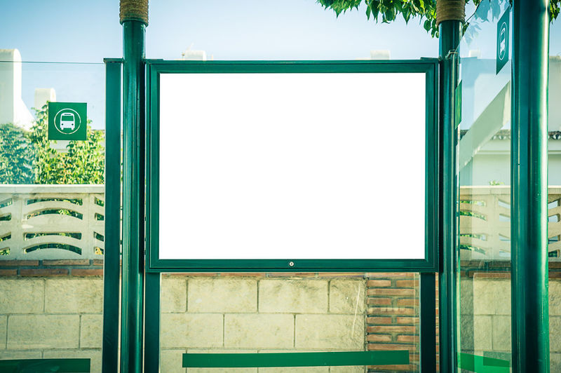 Billboard Advertisement Architecture Blank Building Building Exterior Built Structure City Communication Copy Space Day Door Entrance Glass - Material Green Color Nature No People Outdoors Sign Tree Wall - Building Feature Window