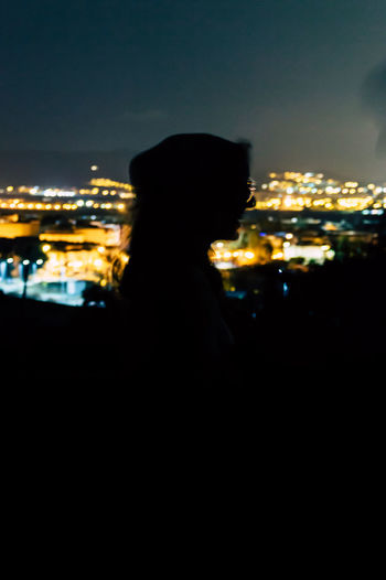 Silhouette man looking at illuminated city against sky at night