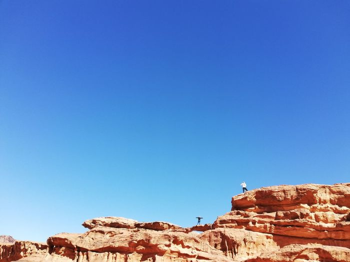 People hovering over the Rock Bridge Selfie Holiday Travel Vacations Wadi Rum Jordan Vertigo People Brave Clear Sky Mountain Blue Desert Sunny Sky Landscape Eroded Rock Formation Geology Natural Landmark Canyon Natural Arch