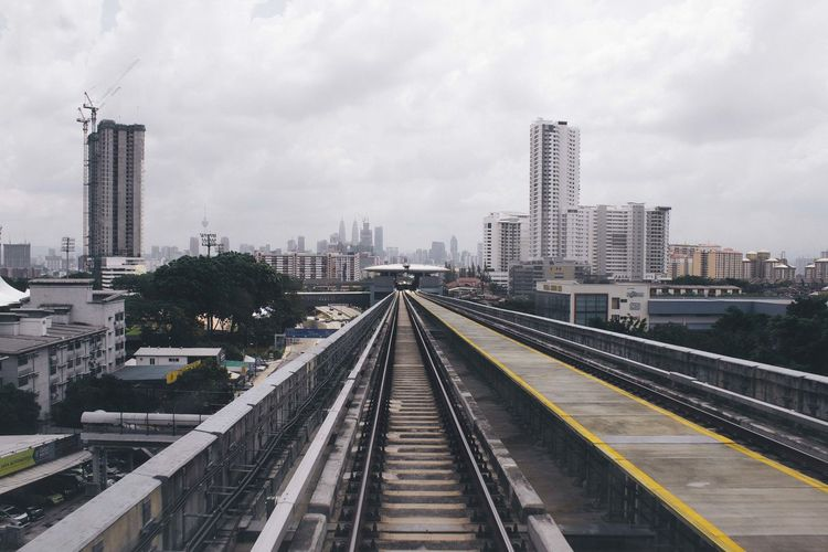 Railway tracks in city against cloudy sky
