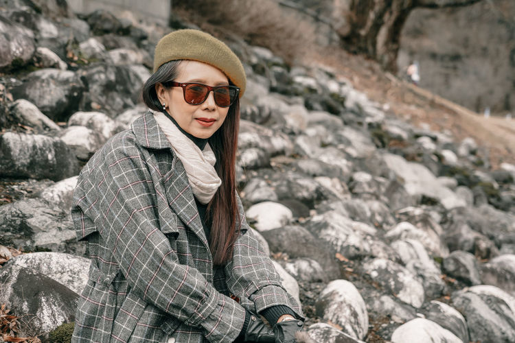 Young woman wearing sunglasses on rock