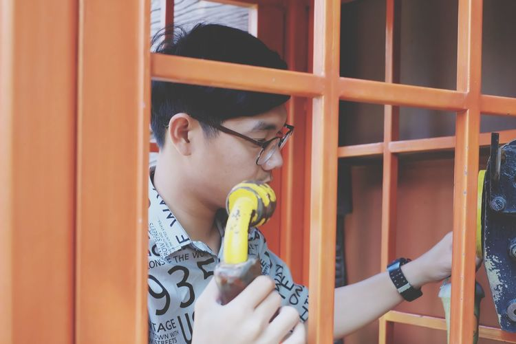 Young man standing in telephone booth