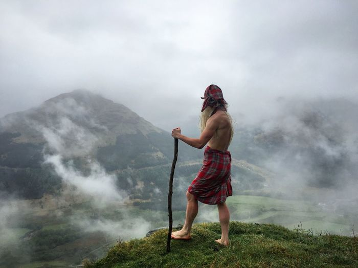 Man standing on mountain against cloudy sky in foggy weather