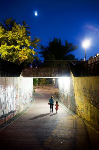nature above, concrete below, humans among them Daughter And Mother Moon Night Lights Underground Passage City Graffiti Wall Moving Away From Camera Night Tree Two People Walking First Eyeem Photo