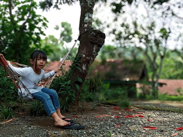 Full length of girl sitting on hammock against trees