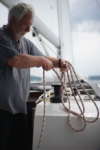 Senior man working on sailboat against sky
