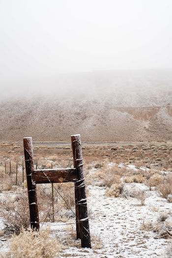 snow on wooden fence posts in snowy desert landscape with cattle tracks in snow on ground with fog and mist obscuring the red hills in distance Fog Landscape Nature No People Environment Day Absence Sky Scenics - Nature Tranquility Copy Space Outdoors Abandoned Land Tranquil Scene Rural Scene Old Winter Beauty In Nature Climate Snow Covered Fence Post Desert Landscape California Desert
