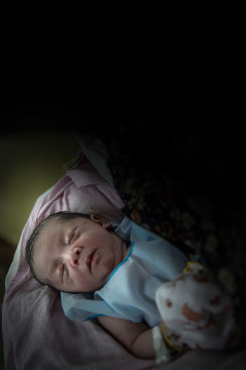Cute baby boy sleeping on bed