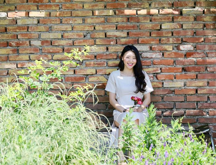 Smile Photo Lovely One Person Young Adult Lifestyles Plant Brick Wall Leisure Activity Young Women Women Long Hair Real People Wall Looking At Camera