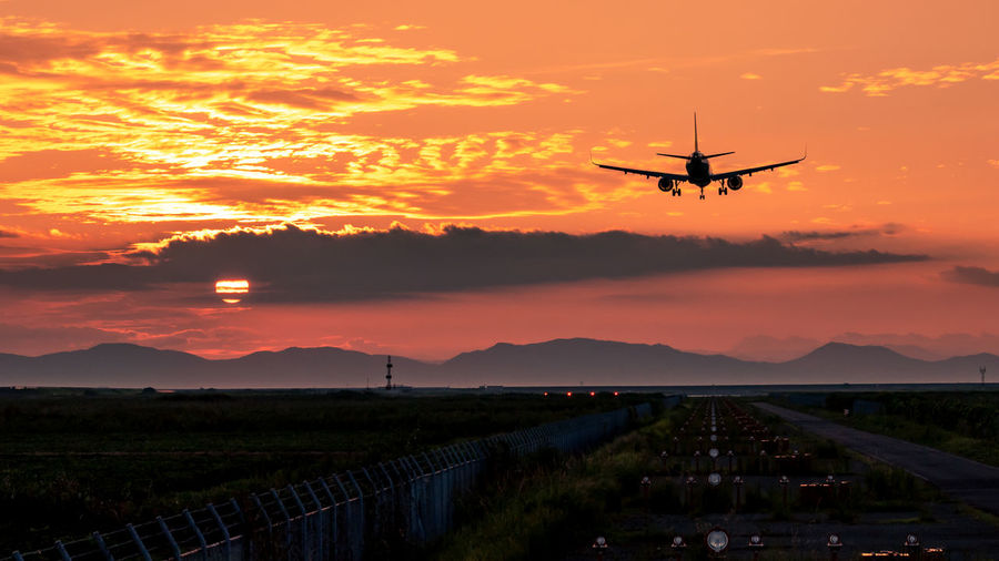 Aerospace Industry Air Vehicle Airplane Airport Airport Runway Beauty In Nature Cloud - Sky Environment Flying Mid-air Mode Of Transportation Mountain Nature No People Orange Color Outdoors Scenics - Nature Sky Sunset Transportation Travel