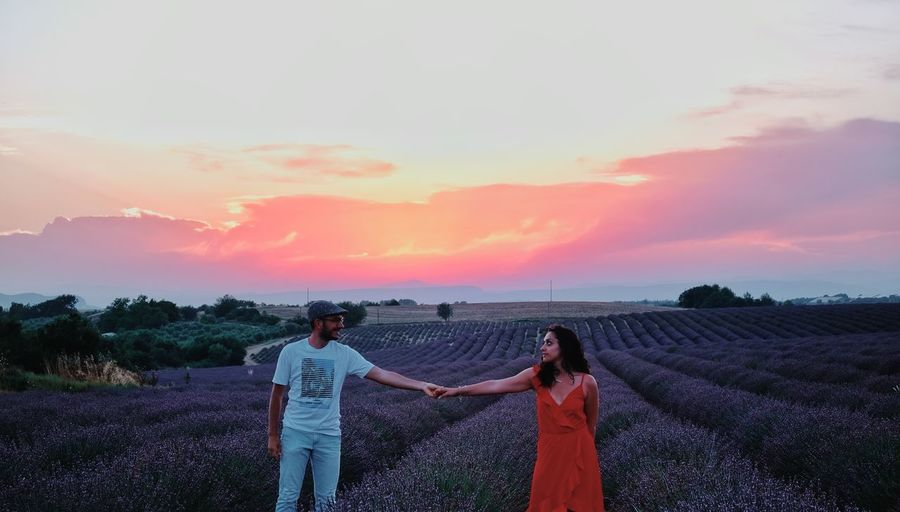 People standing on field against sky during sunset