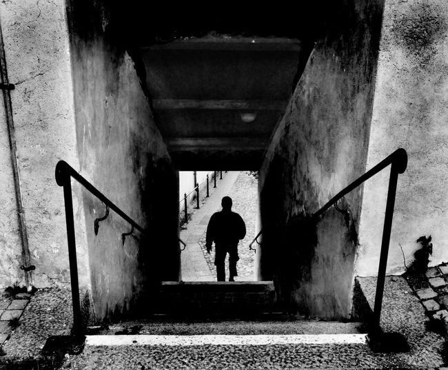 Unrecognizable person going down stairs Architecture Blackandwhite Built Structure Day Full Length Hand Rail Lifestyles Men One Person Outdoors People Real People Rear View Silhouette Staircase Standing Steps Steps And Staircases The Way Forward Unrecognizable Person Walking