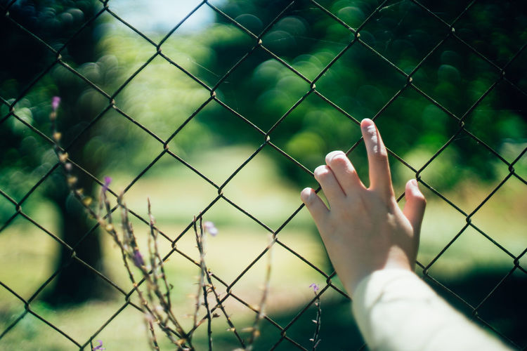 Midsection of person seen through chainlink fence