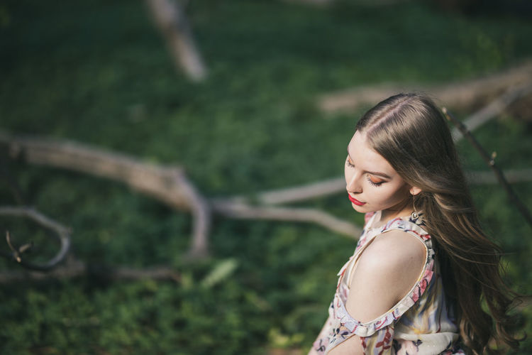 High angle view of beautiful young woman sitting in park