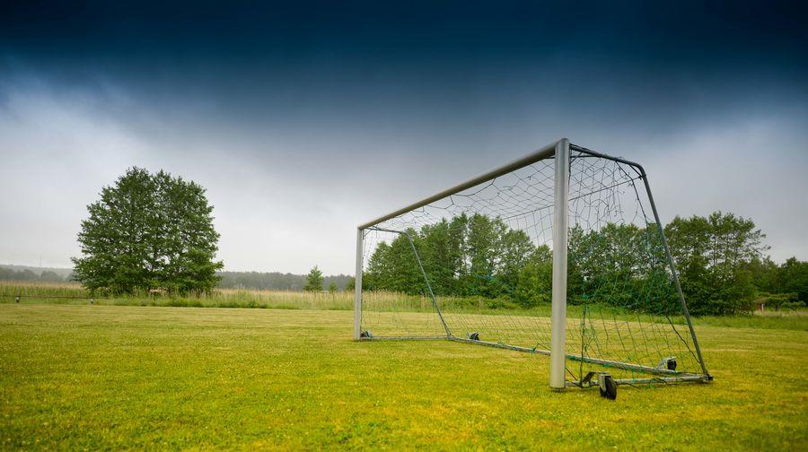 Soccer goal on field against cloudy sky