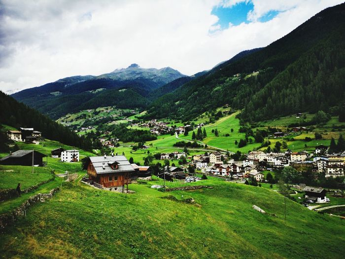 Scenic view of green landscape and buildings against sky