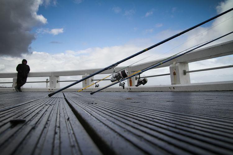 Fishing rods on pier against sky