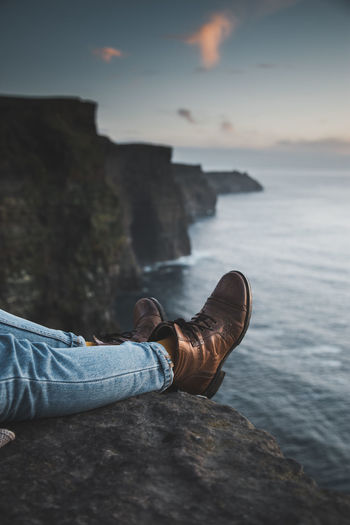 Low section of person wearing shoes on cliff by sea during sunset