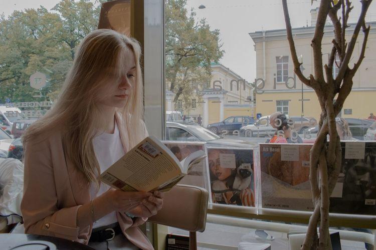 Portrait of woman sitting in glass window