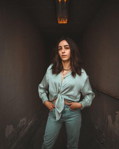 Portrait of woman standing against dark room