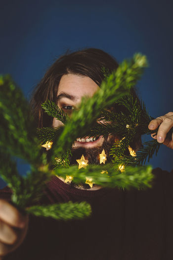 preparing for the fight with a christmas tree Christmas HolidayMarketing Lights Merry Christmas! Beard Beard Decoratio Christmas Decoration Christmas Tree Close-up Human Hand One Person People Portrait Selfportrait Young Adult