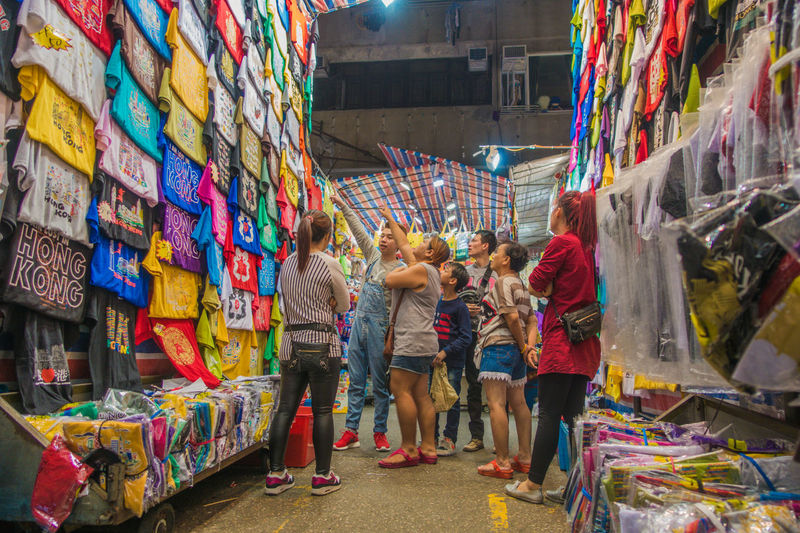 People standing in clothes market at night