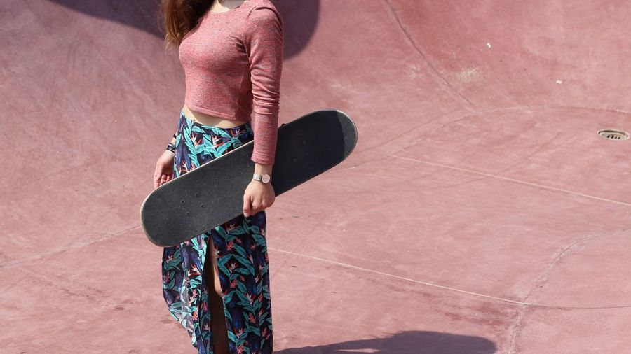 Midsection Of Fashionable Young Woman Holding Skateboard While Standing On Sports Ramp