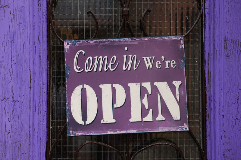 Open Sign Hanging On Purple Door