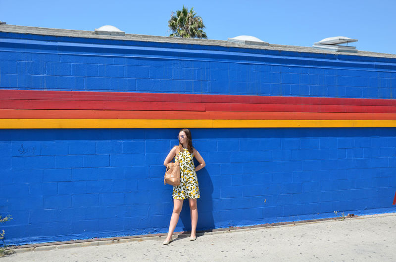 Woman Standing Against Blue Wall During Sunny Day