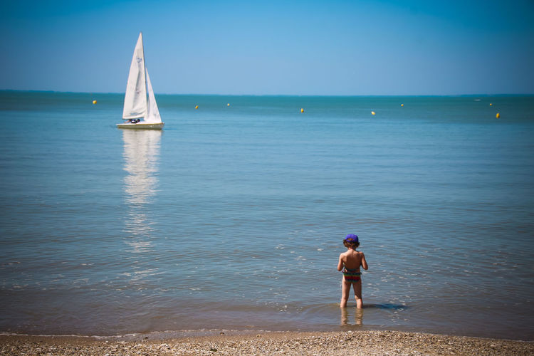Rear View Of Girl Standing On Shore At Beach