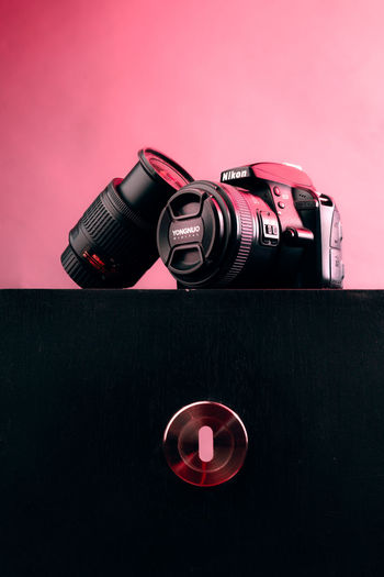 Close-up of camera on table against pink background