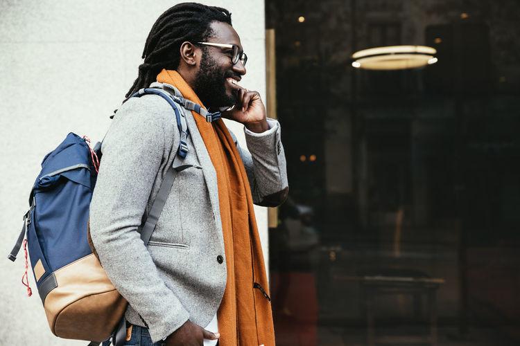 Smiling Man Talking On Mobile Phone While Walking In City