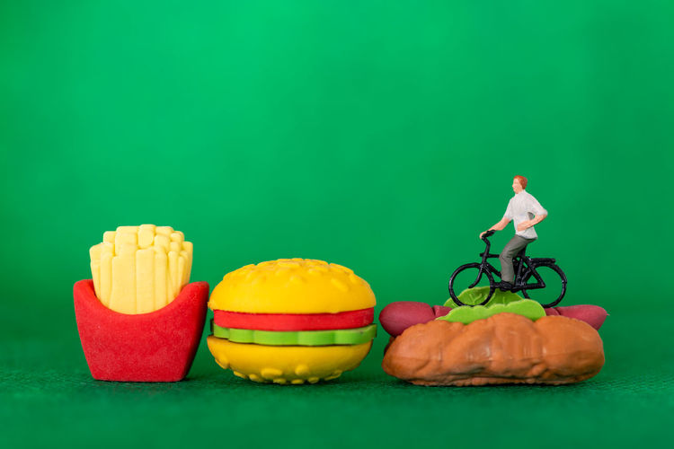 Close-up of toys on table against green background