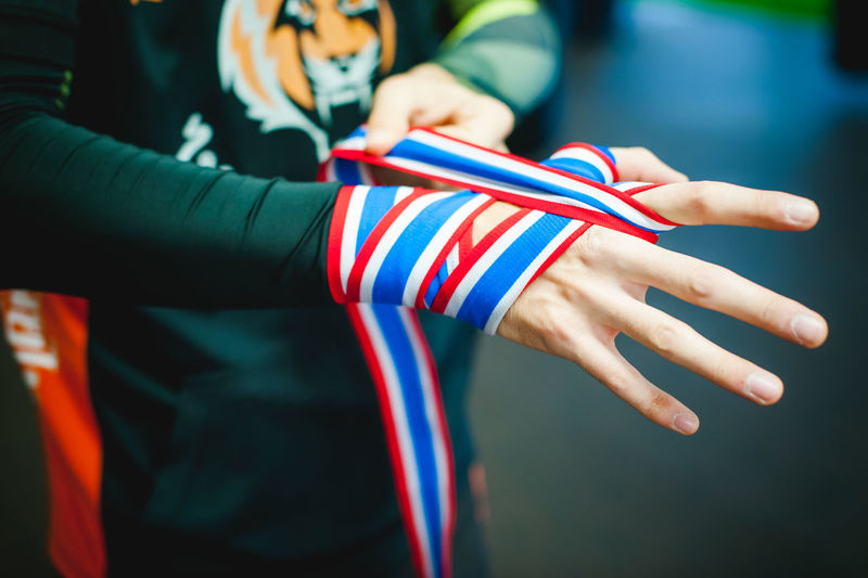 Midsection of man tying ribbon on hand