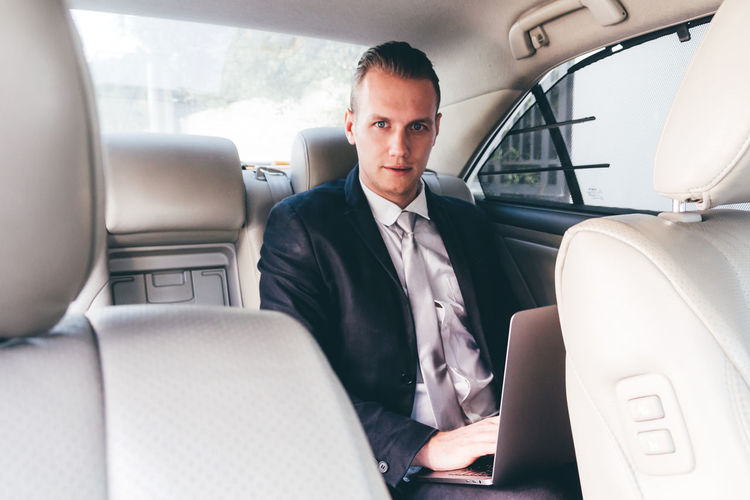Portrait of young businessman using laptop while sitting in car