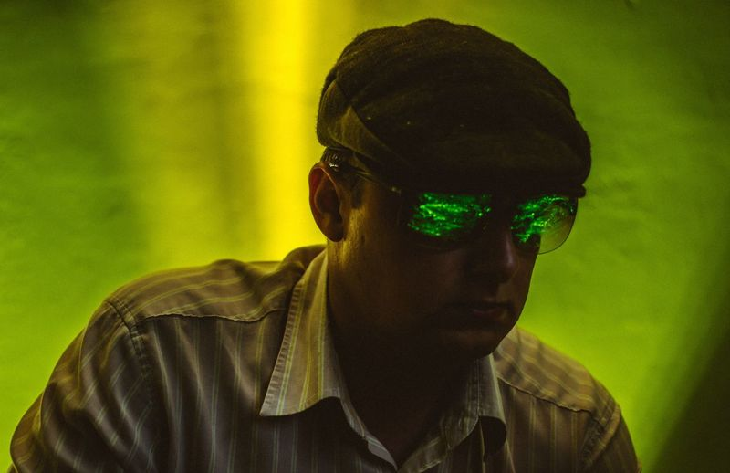 Close-up of mid adult man wearing sunglasses against green illuminated wall
