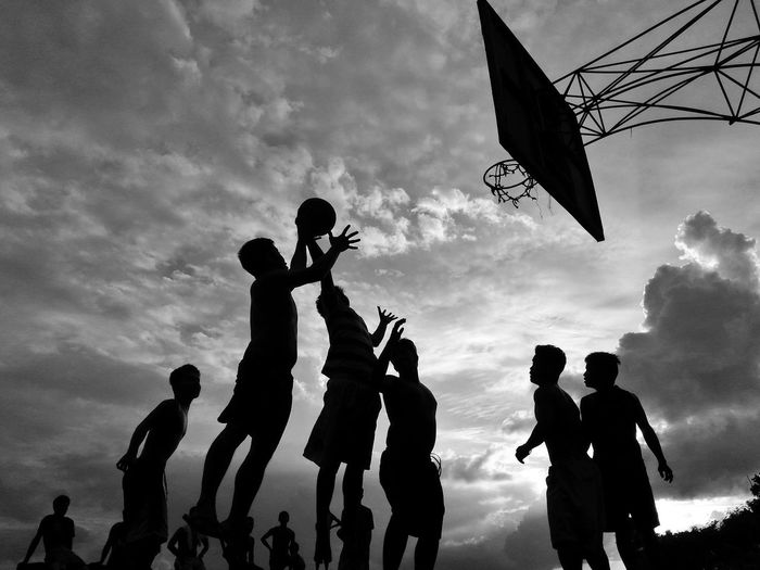 Low angle view of silhouette friends playing basketball against cloudy sky
