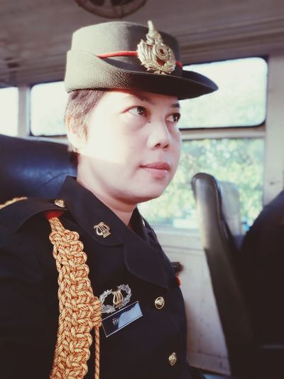Woman wearing uniform while sitting in bus