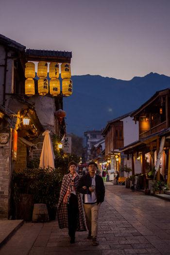 People walking on illuminated building at night