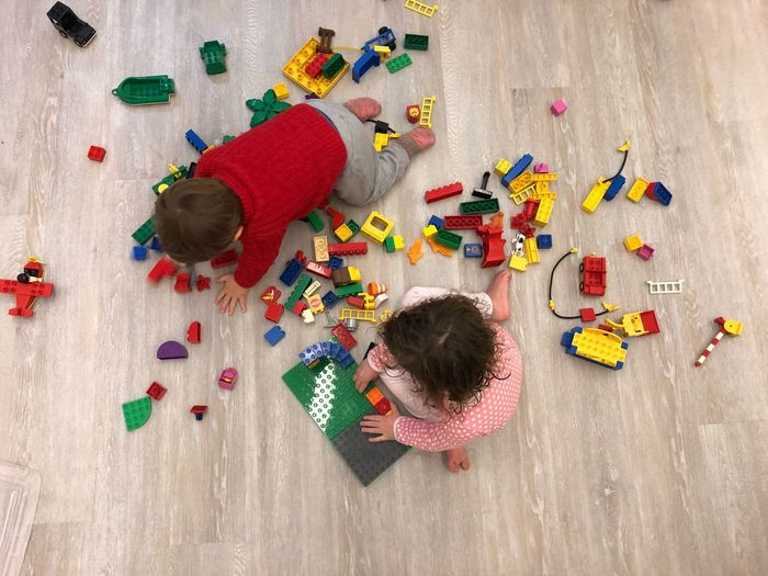 High Angle View Of Children Playing With Toys On Floor