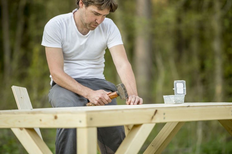 Man holding umbrella on wooden table in yard