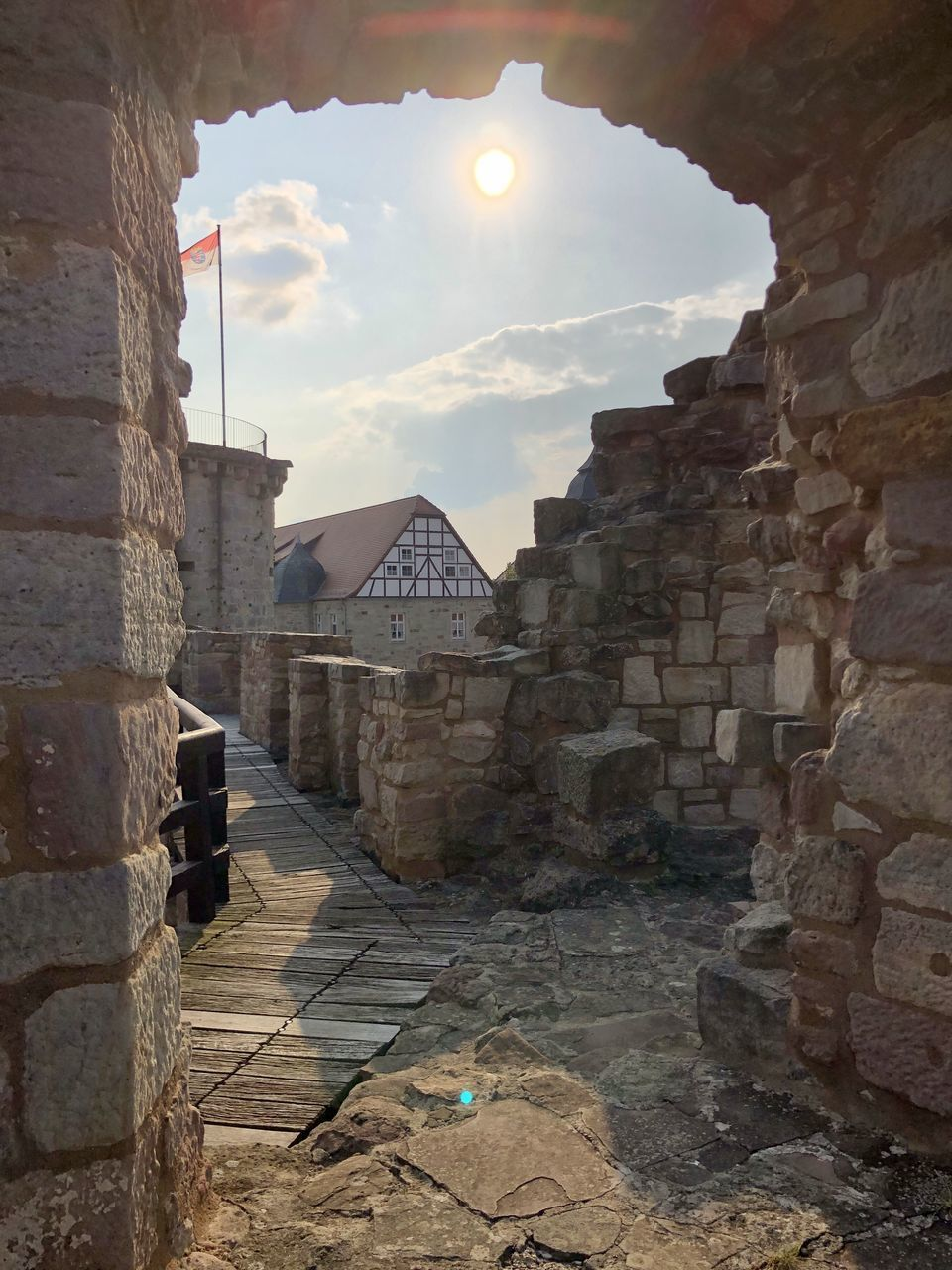architecture, built structure, building exterior, building, history, the past, sky, stone wall, no people, old, nature, wall, ancient, sunlight, cloud - sky, day, travel destinations, wall - building feature, outdoors, residential district, lens flare, ancient civilization