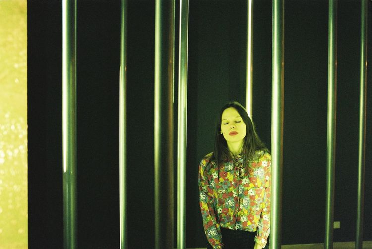 Woman with eyes closed standing by metal bars