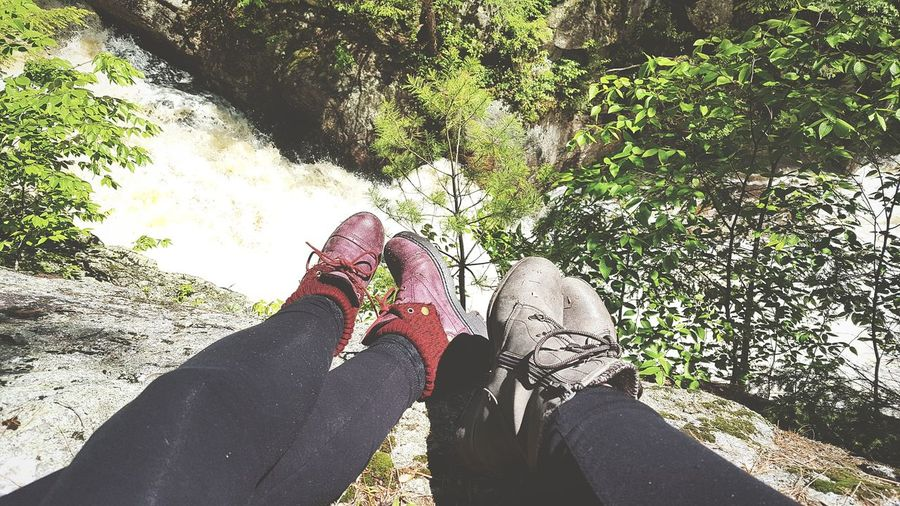Low section of couple relaxing on rock against waterfall