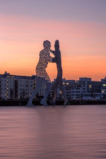 Molecule Men Sculptures In Spree River Against Sky During Sunset