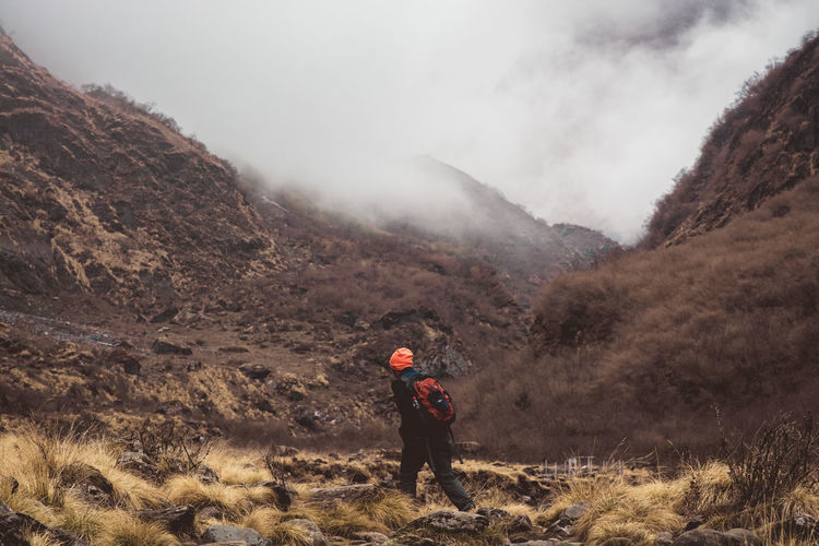 Man walking on field against mountains during foggy weather