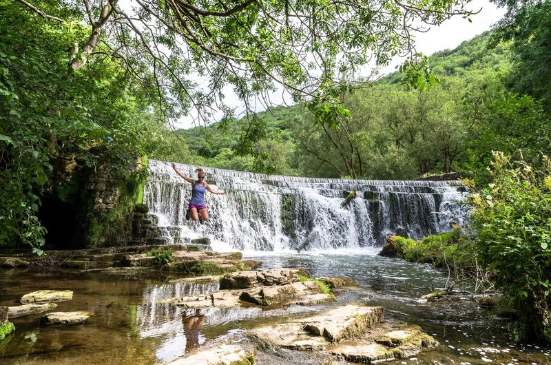 """""""Rewild yourself."""" A woman jumps for joy at a waterfall by the river Wye on the Monsal Trail in the Peak District, England. Waterfalls Adult Vegetation Uk England Rewilding Happiness Adventure Joy Forest WoodLand Plants Summer Peak District  Monsal Dale Forest Woods Waterfall Jumping Jumping For Joy Woman Young Woman Wye Tree Water Nature Growth Day River Flowing Water Summer Exploratorium"""