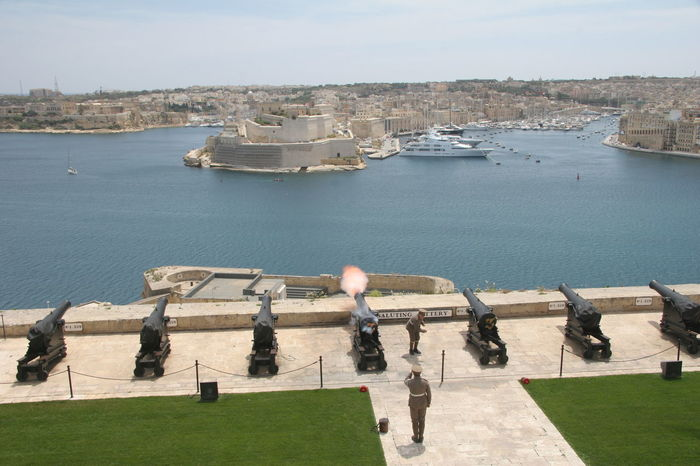 Upper Barrakka Saluting Battery. Entering from the Upper Barrakka Gardens, Valletta's Saluting Battery (Batterija tas-Salut) overlooks Fort St. Angelo and the rest of the Grand Harbour. Once used for firing ceremonial gun salutes, as well as signalling time to the islanders and passing ships, history is brought to life at noon and 4pm daily. The firing of the gun has become one of Malta's most popular visitor attractions. Gun Harbour Salute Saluting Battery Travel Travel Photography Upper Barrakka Gardens Architecture Building Exterior Built Structure Canon Day Fort Gardens Grand Harbour High Angle View Nature Noon Gun Outdoors Sea Ships Sky Travel Destinations Valletta Water