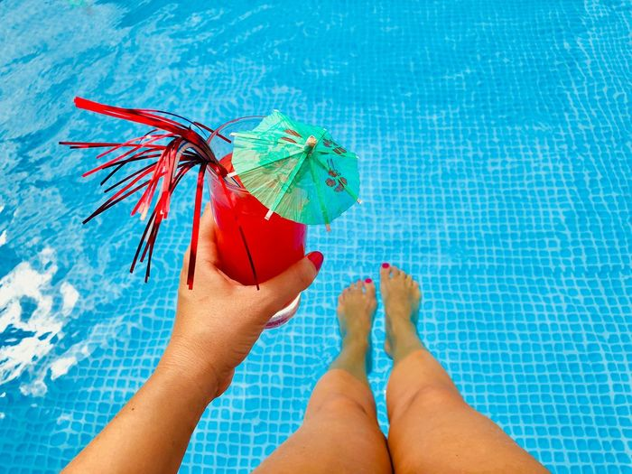 Low section of woman holding drink while sitting by swimming pool