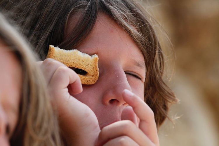 Close-Up Of Boy Looking Through Piece Of Bread